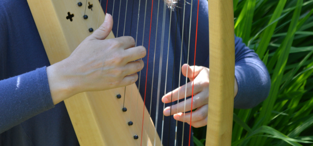 close-up of hands playing a medieval harp