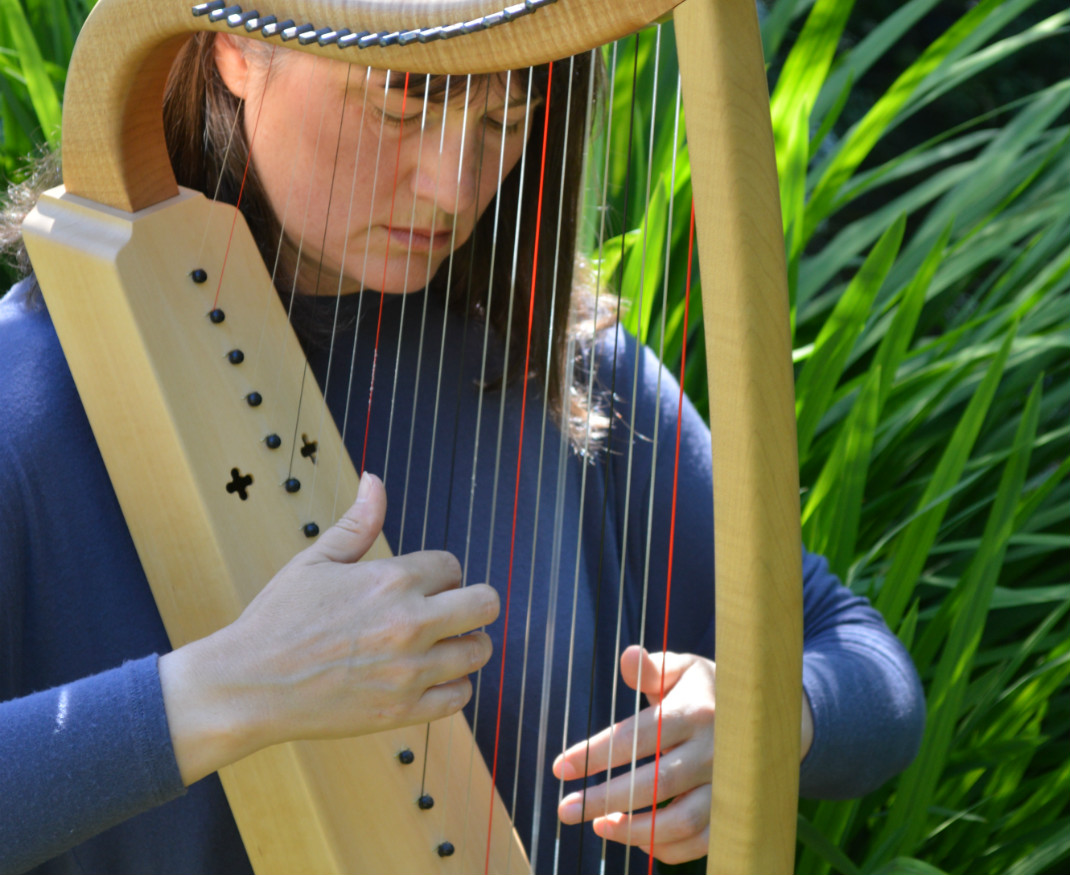 nw playing a medieval harp by green foliage in Cornwall
