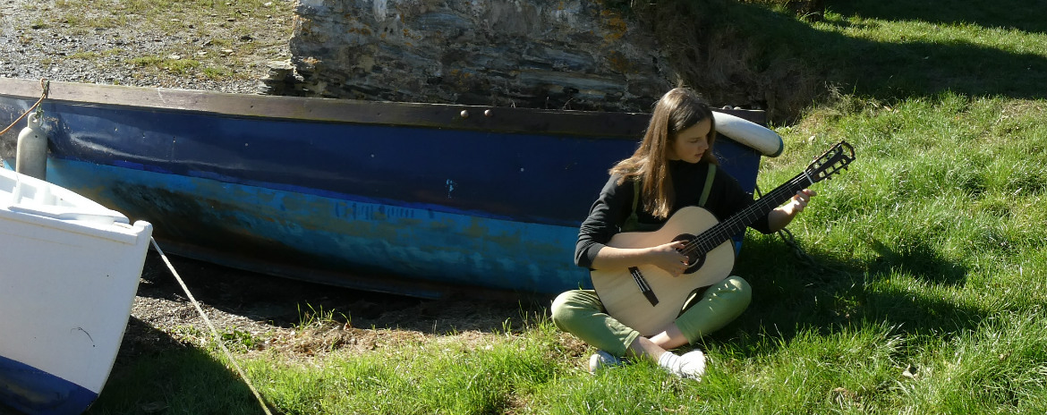girl playing classical guitar in cornwall by a blue boat