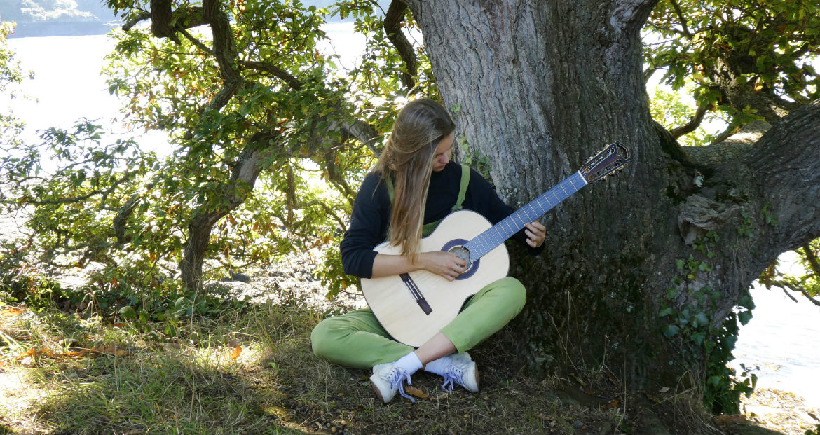 girl playing a classical guitar by a tree in Cornwall